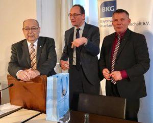 Auf der Mitgliederversammlung der Bayerischen Krankenhausgesellschaft am 14. Dezember 2018 im Bayerischen Landtag: TK-Bayern-Chef Christian Bredl (rechts) und ich bedanken uns bei Franz Stumpf (links) für sein langjähriges Engagement für die Krankenhäuser in Bayern.